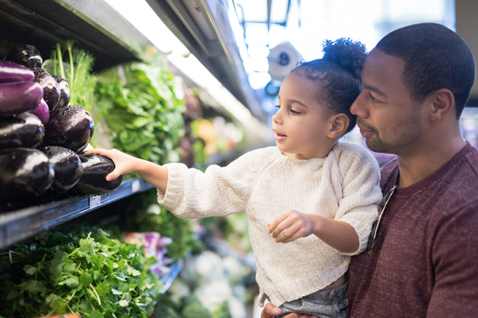 Image of a pre-school age girl helps her dad pick out veggies in the produce section at the grocery store. He is holding her next to the produce and she is picking out eggplant.